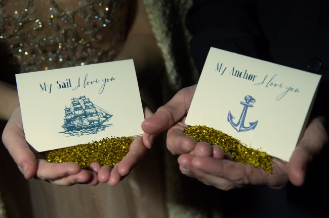 Bride and groom holding nautical themed cards (sailboat and anchor images) and gold glitter