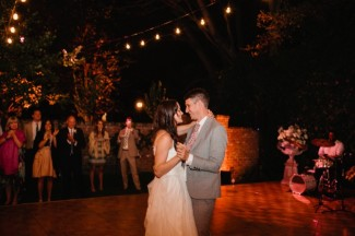 Bride and groom dancing on dance floor in backyard wedding under small hanging lights