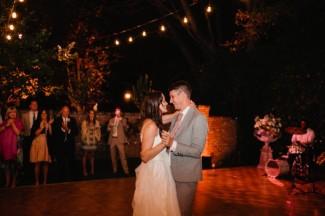 Bride and groom dancing on dance floor in backyard wedding under small hanging lights