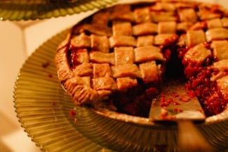 Cheery pie with a slice missing on a green ribbed serving plate