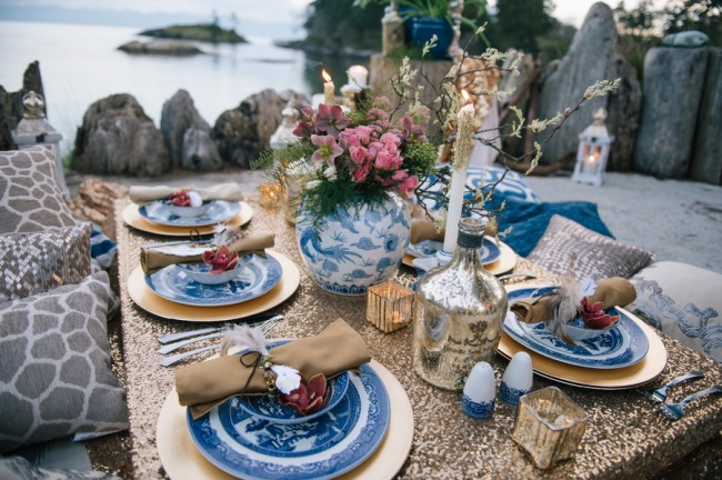 Picnic on water front with gold sequin table cloth, throw pillows, gold chargers and Chinese style plates