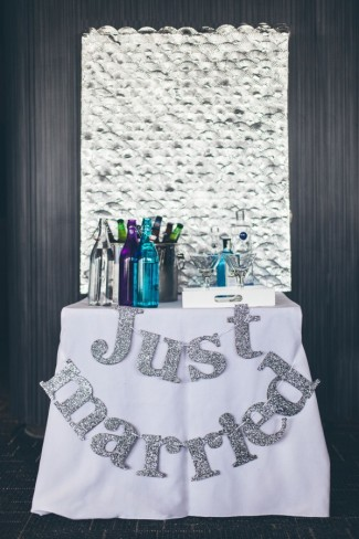 "Bar table with silver glitter ""Just married"" sign hanging from table"