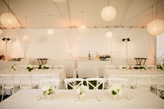 backyard wedding reception under white tent with white tables and chairs and small white floral centerpieces with white lanterns hanging from ceiling.