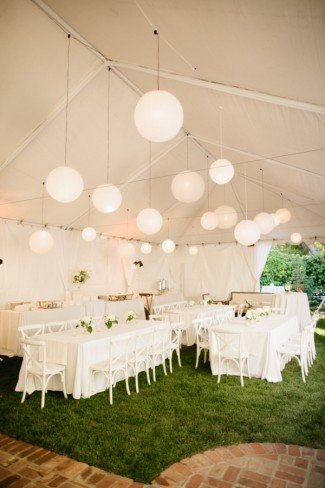 backyard wedding reception tent with white paper lanterns hanging