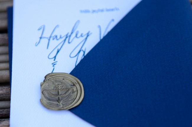 blue envelope with bronze colored seal and white invitation with blue writing