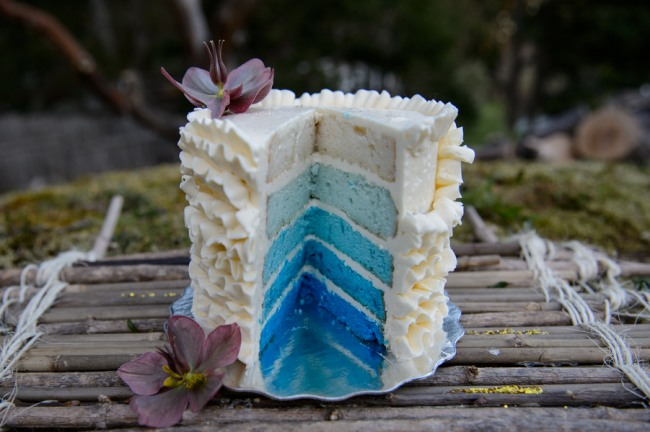 White cake with real purple flowers and blue ombre center.