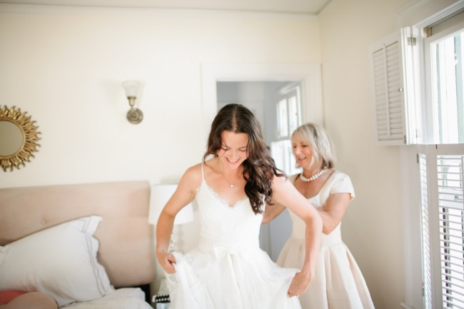 Bride wearing her hair down getting ready in her bedroom with her mom