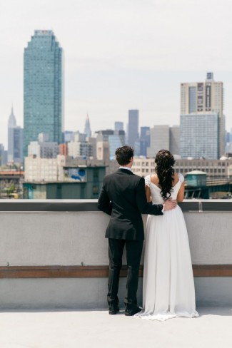 Bride and groom on roof top looking at city scape. Bride wearing a durga-kali dress