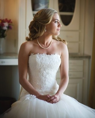 Bride sitting looking to the side wearing a mermaid gown and a pearl necklace