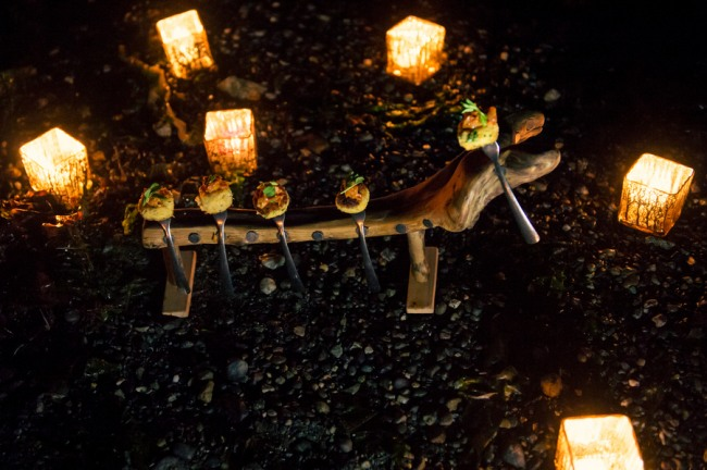 hors d'oeuvres on forks with candle light on West Coast beach at night