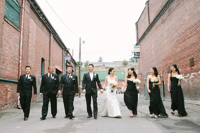 Bride and groom and bridal party wearing black dresses and tuxes walking between two brick buildings