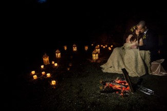 Bride and groom snuggling on the beach with fire and candle light