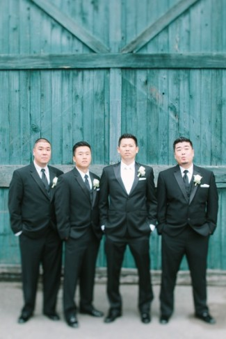 Groomsmen wearing black tuxes standing in front of blue wood wall