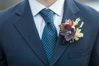 Groom wearing blue and white polka dot tie with purple, white and yellow boutonniere