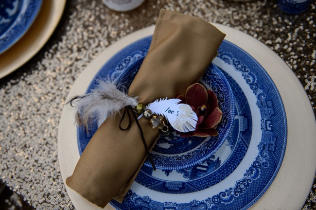 Gold sequin table cloth. Gold charger with Chinese dishes and brown napkin for a place setting. Feather and orchid with place card wrapped with beads.