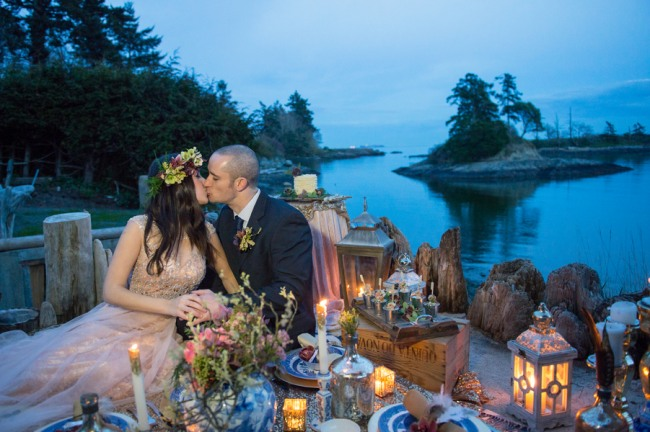 bride and groom kissing on beach front in a boho picnic with candles and lanterns