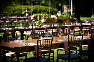 Outdoor wedding reception with long wood tables and brown chevalier chairs and hanging center pieces