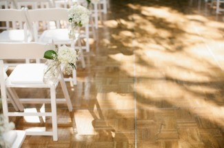 Wedding ceremony with White folding chair with white hydrangea and baby's breath in mason jar hanging from chair