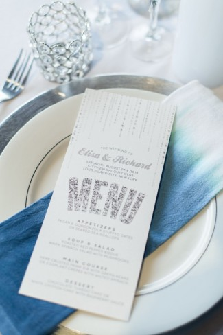 White menu with silver sparkle writing on top of blue ombre napkin and silver charger