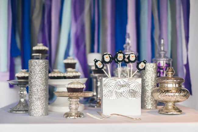 Silver themed dessert table with a purple and blue crepe paper back ground