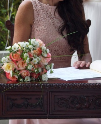 bridesmaid in pink lace dress signing book