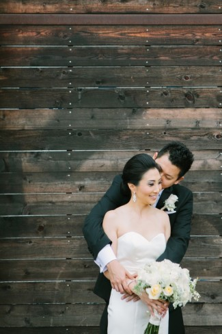 Groom embracing bride standing in front wood wall