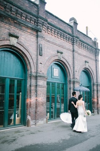 bride and groom walking with parasols beside brick building