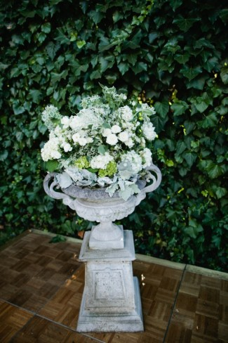 cement urn with white and green floral arrangement for backyard wedding