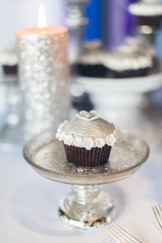 Silver glitter candle in back ground. Cup cake decorated with small white flowers on small glass cake stand