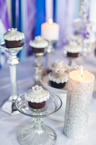 Chocolate cup cakes on small glass cake stands and candle sticks