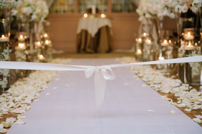 Ceremony aisle with white aisle runner and cream rose petals at Arctic Club Hotel wedding
