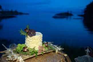 Cream colored cake with purple flowers on wooden raft surrounded foliage. West Coast beach at night in background