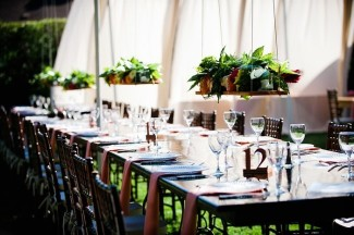 Hanging floral centerpieces in backyard wedding reception with long wood tables and brown chevalier chairs