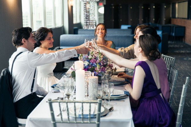 Bride and groom with bridal party have a toast at a purple and silver theme table