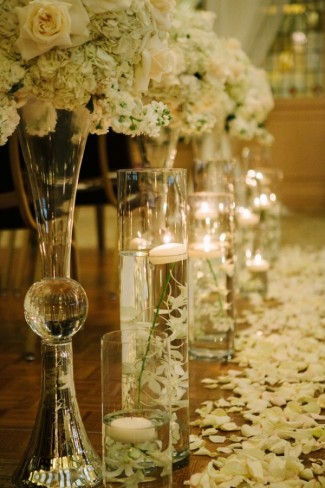 Tall vases with white and cream flowers bouquet and floating candles for ceremony decor at Arctic Club Hotel