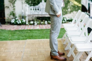 Groom wearing grey suit and brown shoes waiting for backyard ceremony to begin with hands in pockets