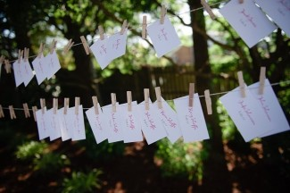Twine line with guests escort cards hanging with clothes pegs for outdoor wedding reception