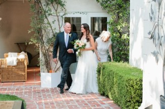 Bride walking down aisle with father in backyard wedding