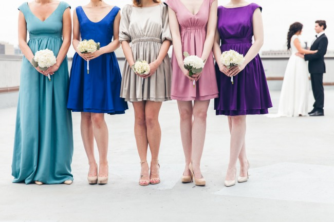 Bridesmaids wearing durga-kali dresses in pink, blue, teal, purple and grey colors holding white flower bouquets. bride and groom in the back ground