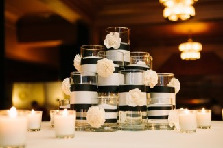 Silver candles with black ribbon stacked like a pyramid with small white flower