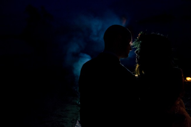 Bride and groom standing in the dark with moonlight silhouette