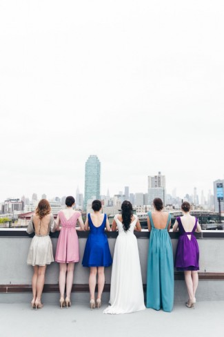 Bride with five bridesmaids wearing durga-kali dresses in pink, blue, teal, purple and grey colors