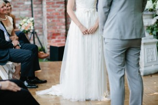 bride and groom standing at the front during backyard wedding ceremony. Groom wearing grey suit
