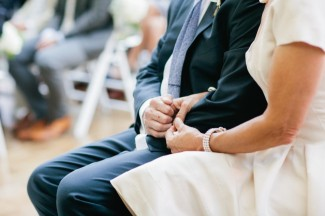 photo of bride's parents holding hands during wedding ceremony