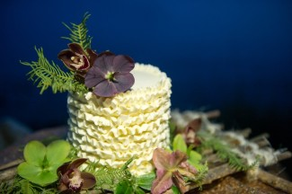 Closeup: Cream colored cake with purple flowers on wooden raft surrounded foliage.