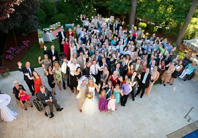 Overhead group photo of all wedding guests waving in backyard