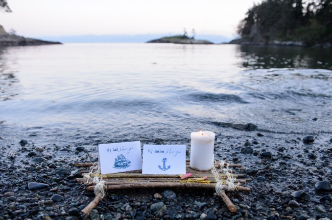 Two nautical themed cards on a small wooden raft sit on rocky West Coast beach with white candle burning