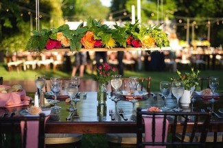 Hanging floral centerpieces overtop long wood tables and brown chevalier chairs