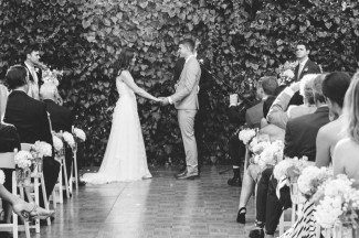 bride and groom holding hands during intimate backyard wedding ceremony