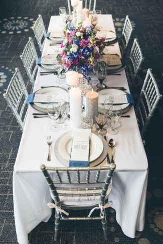 Silver and purple themed wedding reception table with silver chiavari chairs